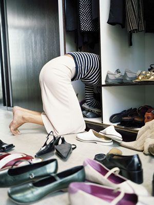 Woman on knees searching through shoes in wardrobe