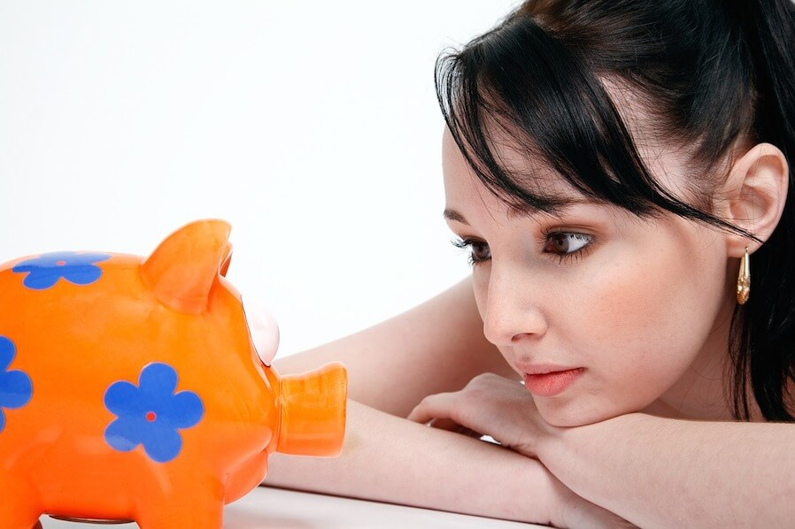 girl staring at a piggy bank