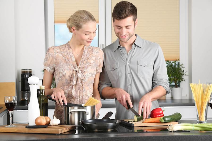 man and woman preparing meal together in the kitchen
