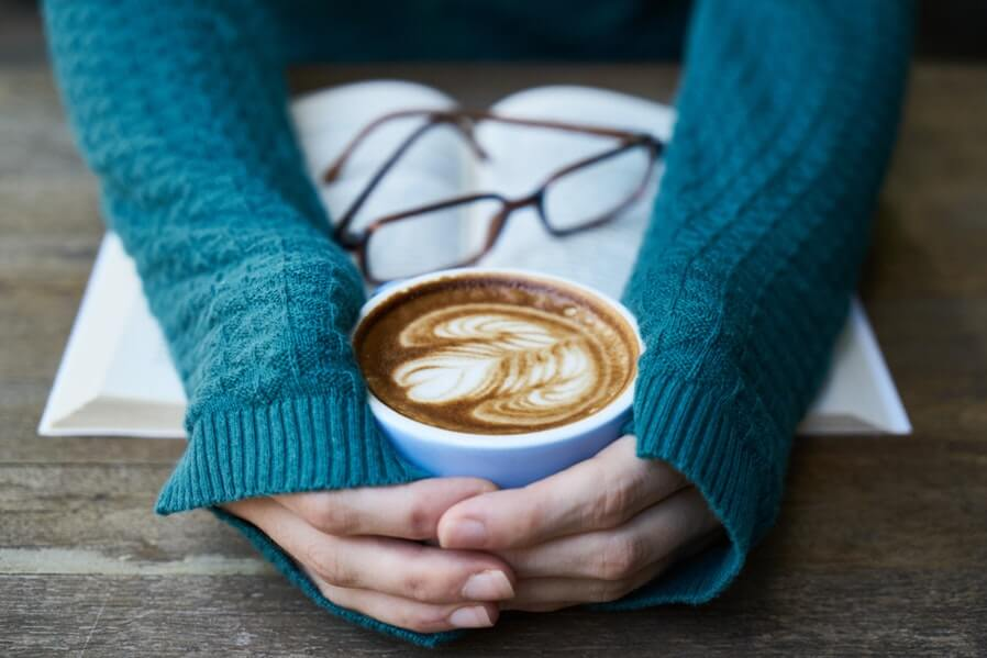 person in blue sweater have coffee and book