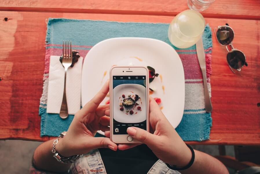person taking a photo of food for social media