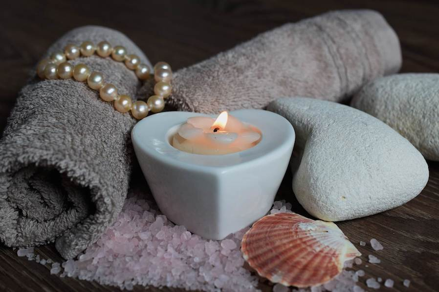 spa essential towels, aromatic candles, and decorations
