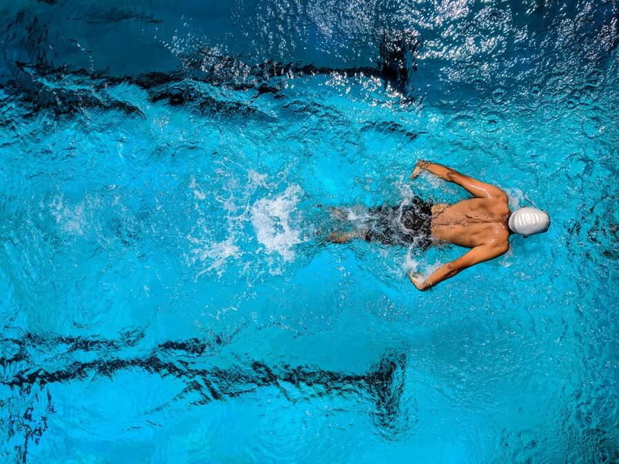 top view photo of man swimming in a pool