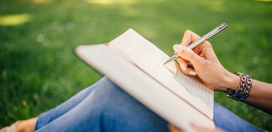 woman's hand writing in notes in notebook