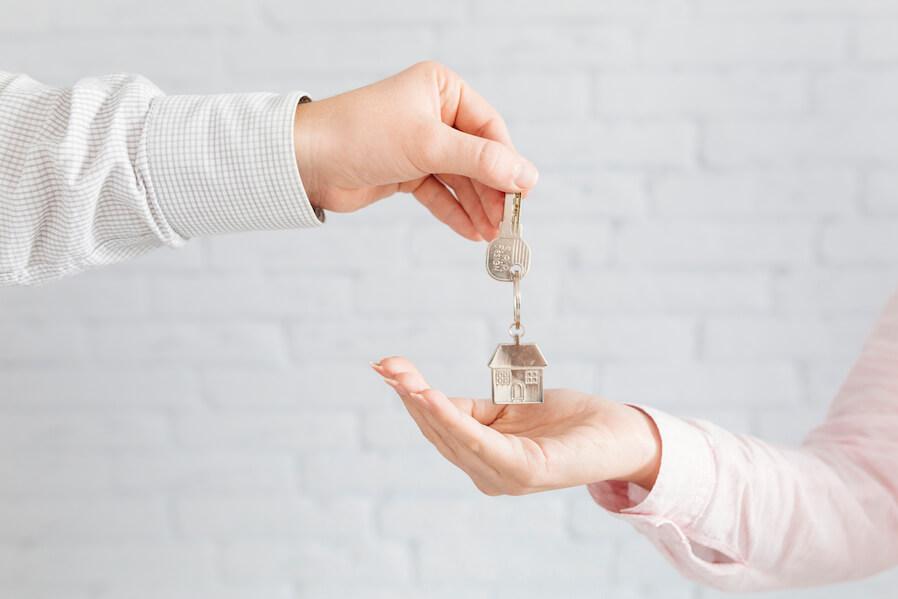 Human hands passing house keys