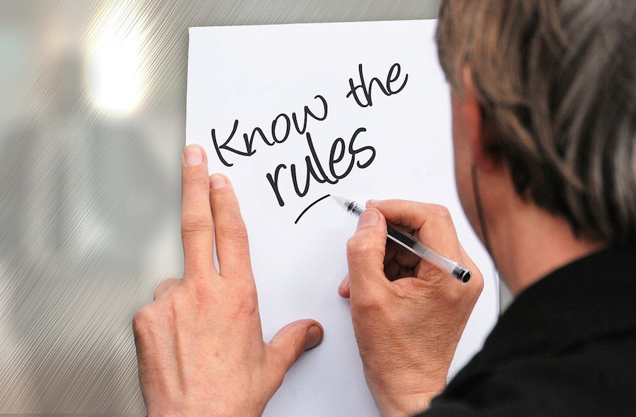 Man writing rules on white paper