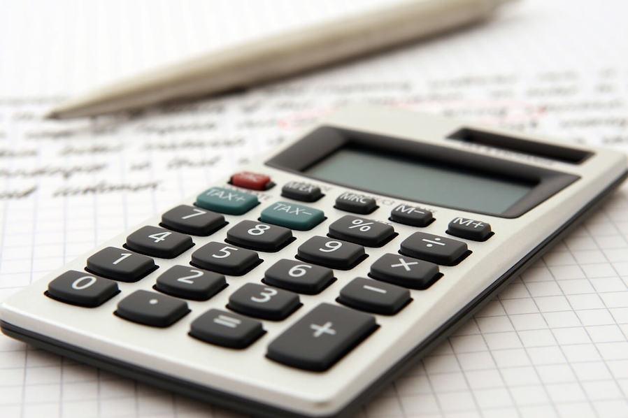 manual calculator, pen, and paper