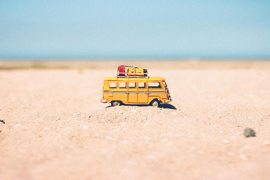 miniature yellow bus on sand