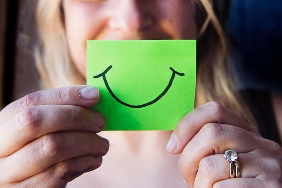 woman holding a smile drawn in green paper
