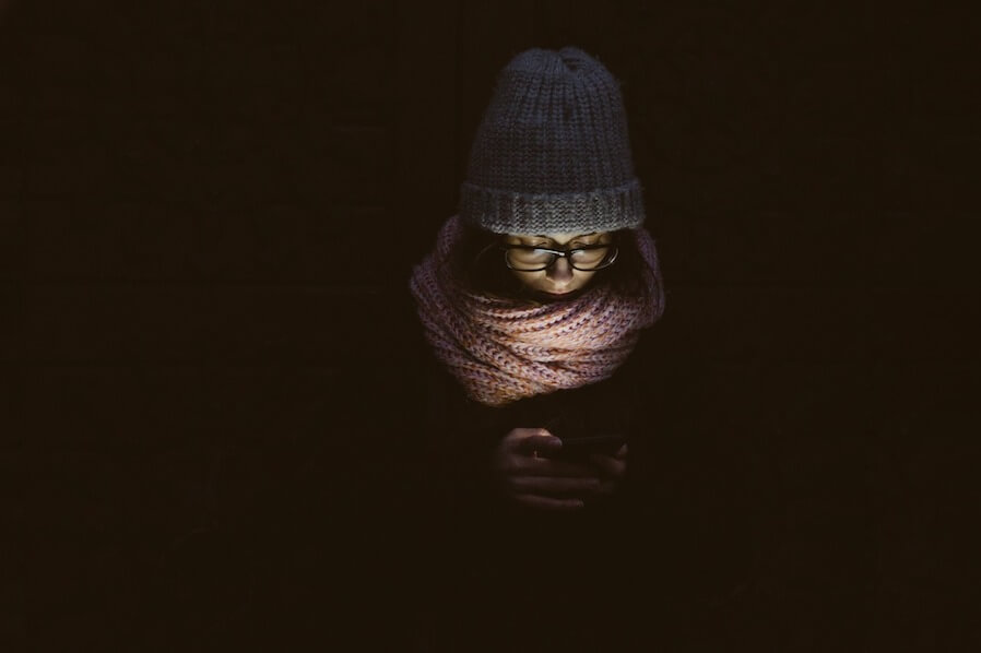 woman in dark setting reading something in her mobile device
