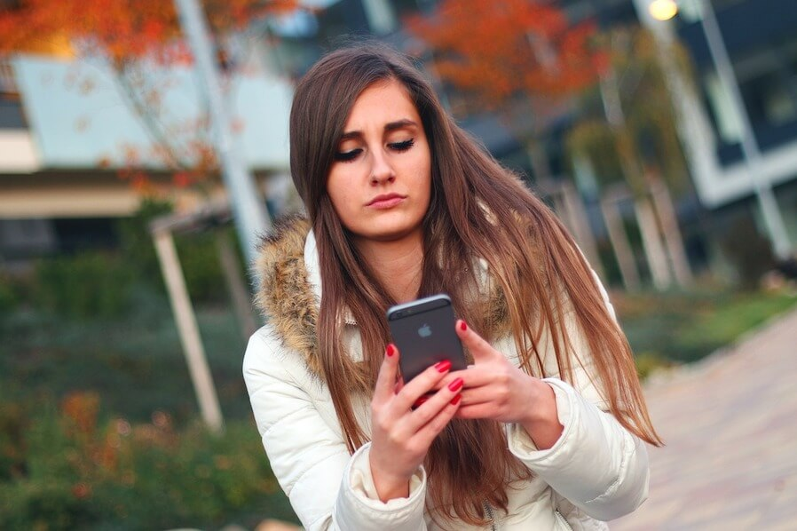 young woman seriously checking her phone