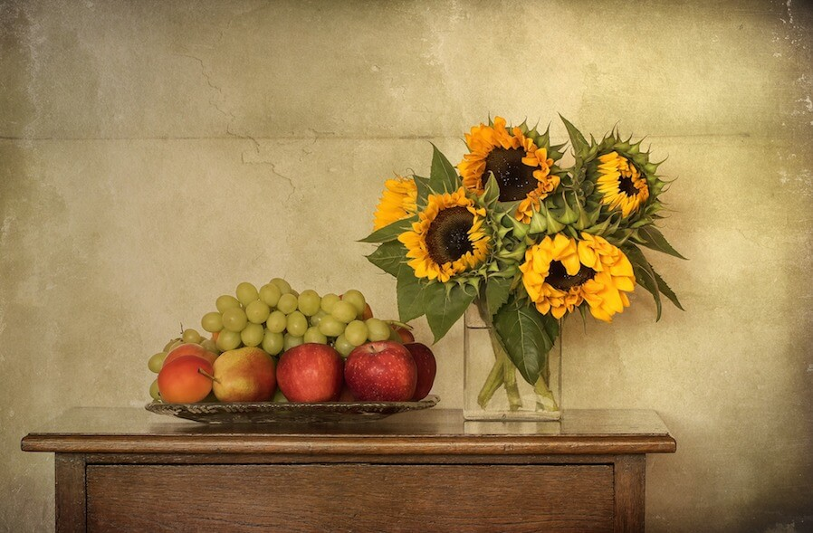 real sunflowers on table next to basket of fruits