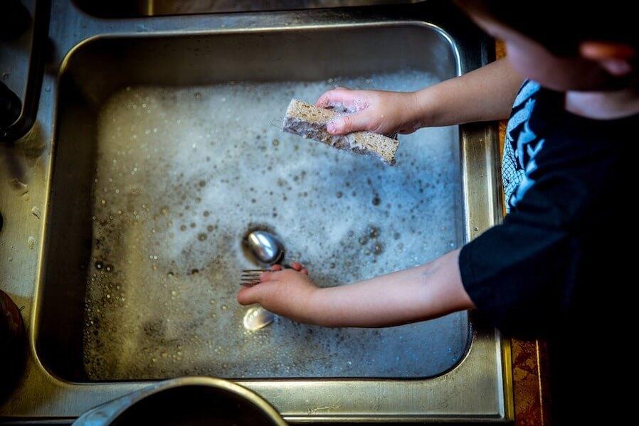 child washing utensils