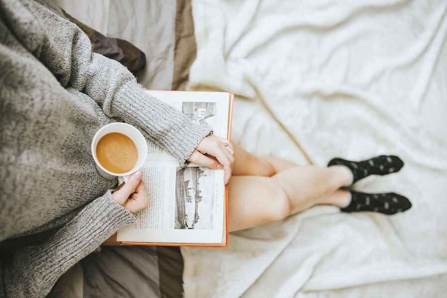 woman reading book and holding a coffee