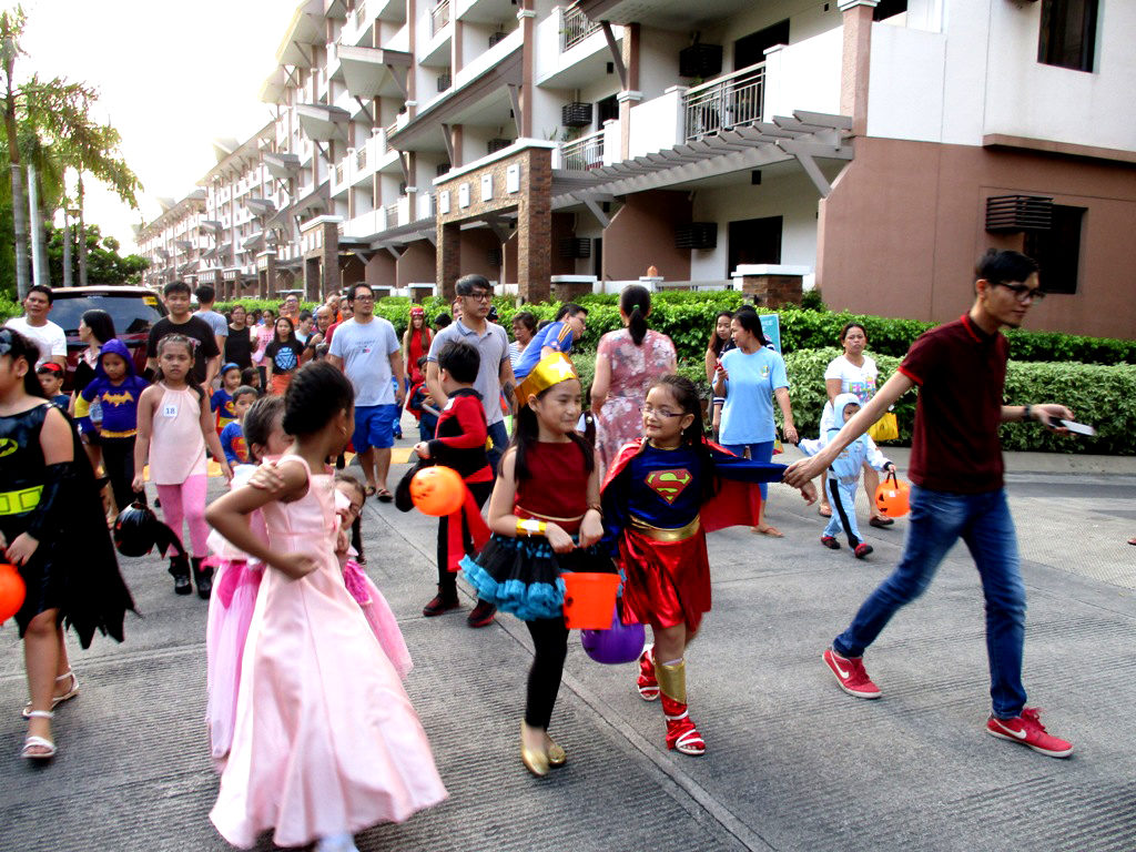 A parade of trick or treaters marched as they look for candies.