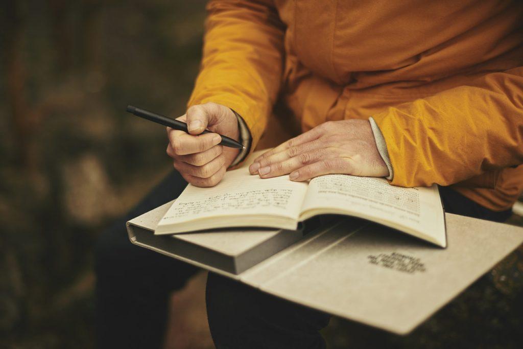 man writing diary