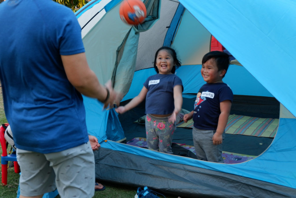 Kids inside a tent having a feel of where they would spend the night in.