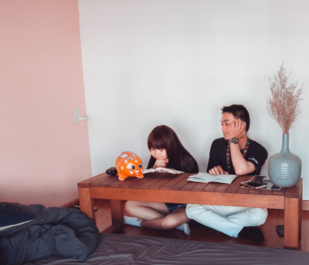 girl and boy sitting in front of brown wooden coffee table