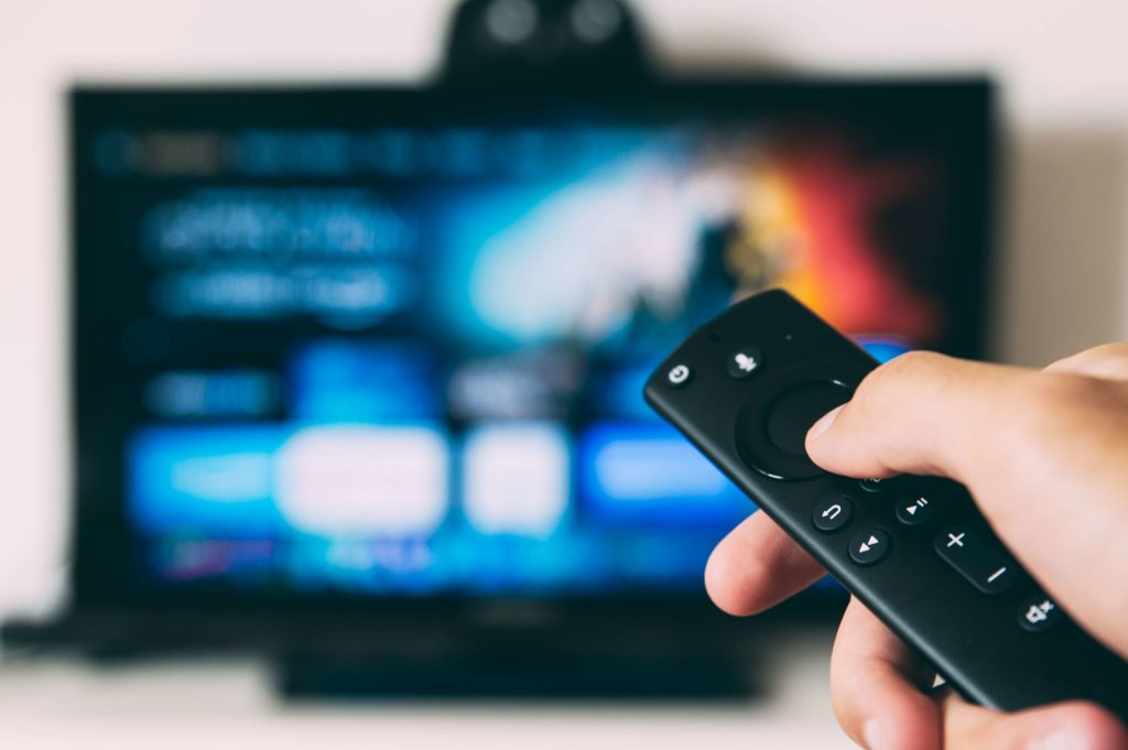 man holding remote to turn on tv