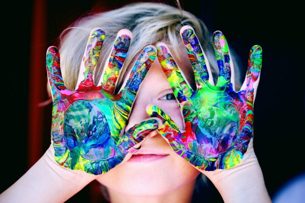 kid with paint in hands