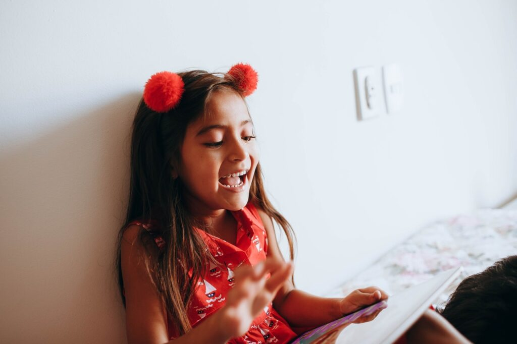 photo of girl leaning on white wall while playing with